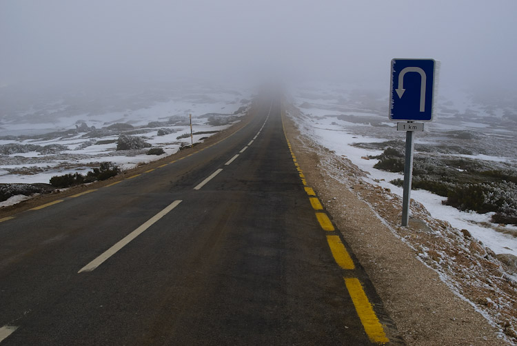 Road leading into mist, with a U-Turn sign to the right.